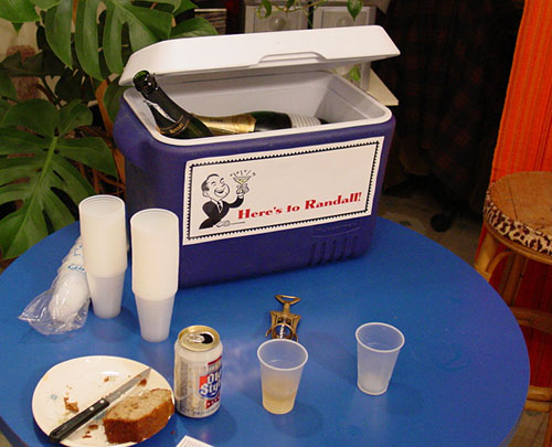 "This is a photo of a cooler full of champagne with a sign that says ""Here's to Randall."""
